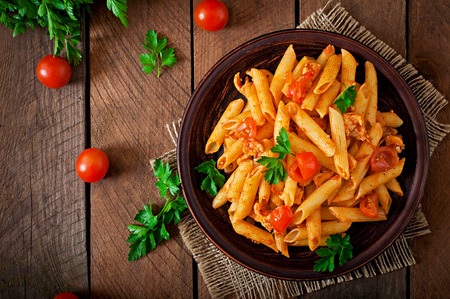 food dish: Penne pasta in tomato sauce with chicken, tomatoes on a wooden background