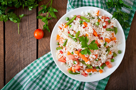 steamed: Appetizing healthy rice with vegetables in white plate on a wooden background