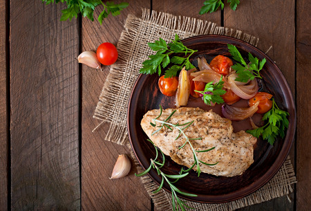 hot breast: healthy baked chicken breast with vegetables on a ceramic plate in a rustic style.