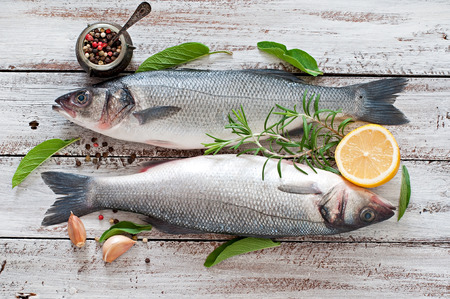 Two raw seabass with spices on an old wooden background. Foto de archivo