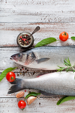 whitefish: Two raw seabass with spices on an old wooden background. Stock Photo