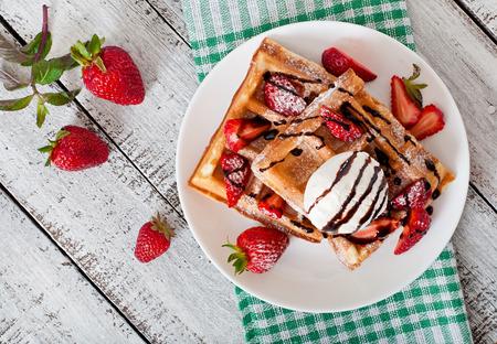 postres: Gofres belgas con fresas y helado en un plato blanco