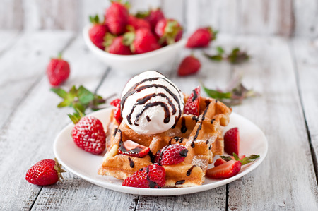 Belgium waffles with strawberries and ice cream on white plate