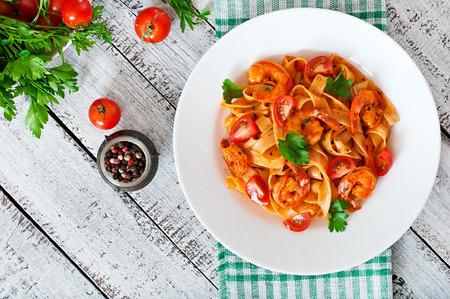 italienisches essen: Fettuccine Pasta mit Garnelen Tomaten und Kräutern Lizenzfreie Bilder