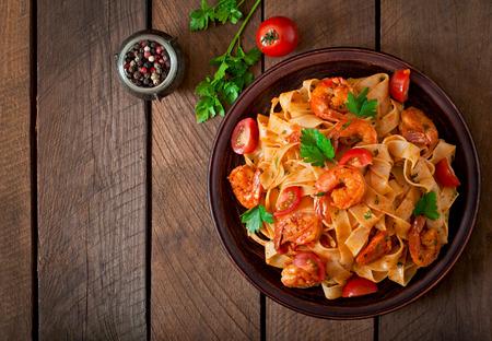 italienisches essen: ettuccine Nudeln mit Garnelen Tomaten und Kräutern