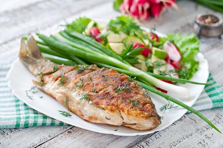 Fried fish carp and fresh vegetable salad Stock Photo