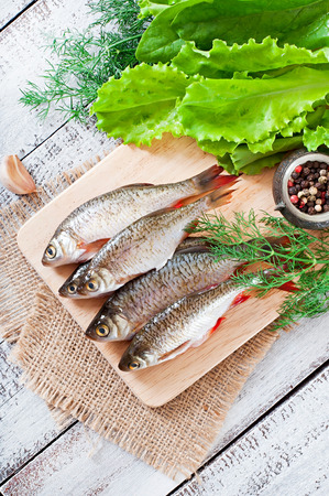 european roach: Prepared for frying fish roach on the wooden background. Stock Photo