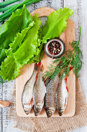dace: Prepared for frying fish roach on the wooden background. Stock Photo
