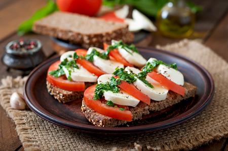 comiendo pan: Bocadillos diet�ticos �tiles mozzarella con tomate y pan de centeno Foto de archivo