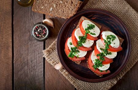 comida italiana: Bocadillos dietéticos útiles mozzarella con tomate y pan de centeno Foto de archivo
