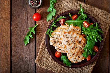 pechos: Pechuga de pollo con ensalada de rúcula y tomate fresco Foto de archivo