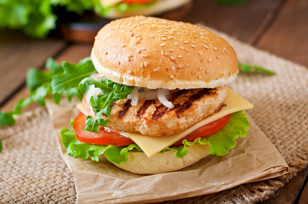 chicken breast: Sandwich with chicken burger tomatoes cheese and lettuce