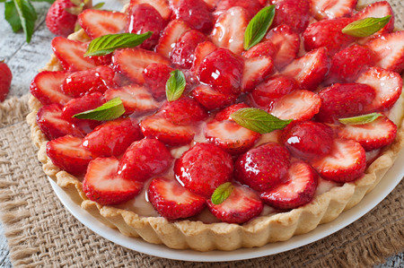 short crust pastry: Tart with strawberries and whipped cream decorated with mint leaves Stock Photo