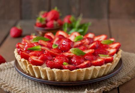 Taart met aardbeien en slagroom versierd met muntblaadjes
