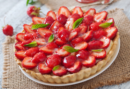 Tart with strawberries and whipped cream decorated with mint leaves Archivio Fotografico