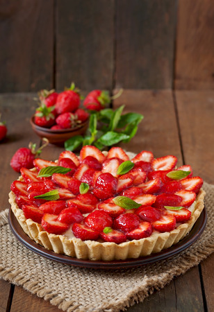 Tart with strawberries and whipped cream decorated with mint leaves Imagens