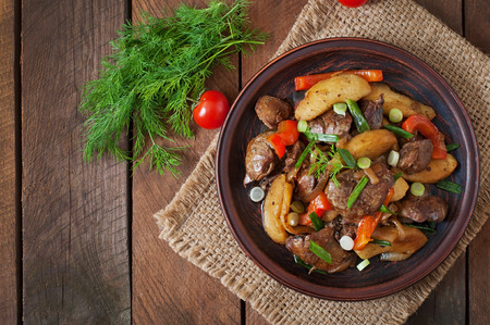 food dish: Roast chicken liver with vegetables on wooden background