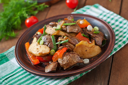 innards: Roast chicken liver with vegetables on wooden background
