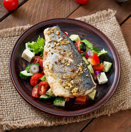 plato de pescado: Lubina al horno con ensalada griega Foto de archivo