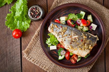pescado frito: Lubina al horno con ensalada griega Foto de archivo