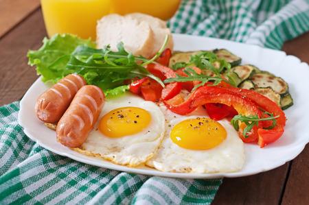 huevos fritos: Desayuno Ingl�s - huevos fritos, salchichas, calabac�n y pimientos dulces Foto de archivo