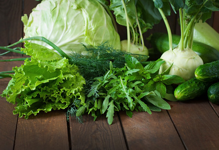 Useful green vegetables on a wooden background Imagens