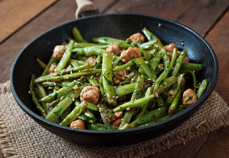 Green beans fried with chicken meatballs and garlic Asian style Archivio Fotografico