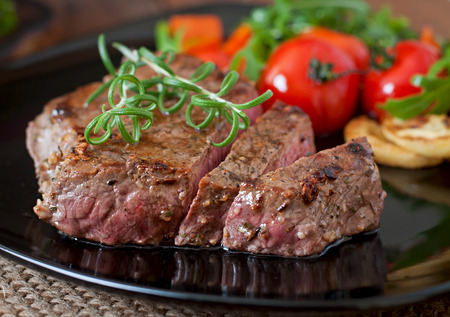 half cut: Closeup of grilled beef steak with vegetables