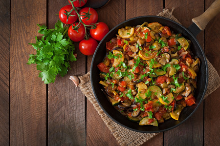 zucchini vegetable: Vegetable Ratatouille in frying pan on a wooden table