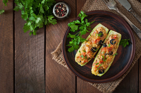 Stuffed zucchini with chicken, tomatoes and olives with cheese crust