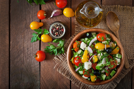 verduras verdes: Ensalada griega con verduras frescas, queso feta y aceitunas negras Foto de archivo