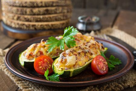 baked meat: Stuffed zucchini with chicken, tomatoes and onion with cheese crust Stock Photo