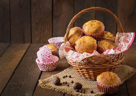 canasta de panes: Magdalenas de frutas con nuez moscada y la pimienta de Jamaica en una cesta de mimbre en un fondo de madera Foto de archivo