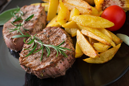 steaks: Tender and juicy veal steak medium rare with French fries
