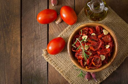 sundried: Sun-dried tomatoes with herbs and garlic in wooden bowl Stock Photo