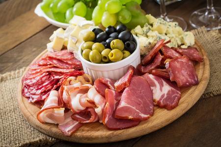 ケータリングとベーコン、ジャーキー、サラミ、チーズ、木製の背景のブドウの盛り合わせ前菜