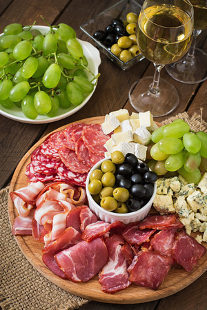 antipasto platter: Antipasto catering platter with bacon, jerky, salami, cheese and grapes on a wooden background