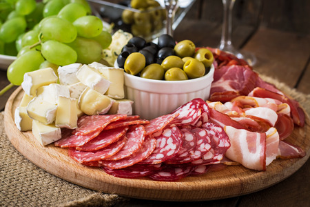 buffet lunch: Antipasto catering platter with bacon, jerky, salami, cheese and grapes on a wooden background