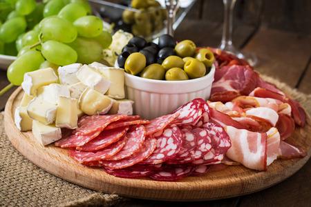 Antipasto ristorazione con piatto di pancetta, a scatti, salame, formaggio e uva su un fondo in legno
