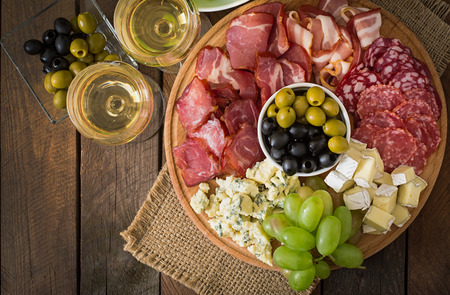 antipasto platter: Antipasto catering platter with bacon, jerky, salami, cheese and grapes on a wooden background. Stock Photo