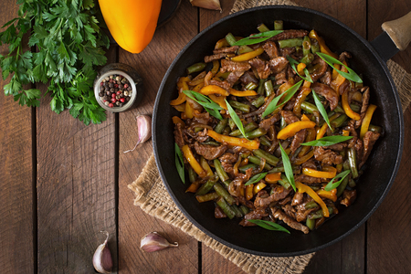 Stir frying beef with sweet peppers and green beans Imagens - 44360304