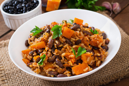 black dish: Mexican vegan vegetable pilaf with haricot beans and pumpkin