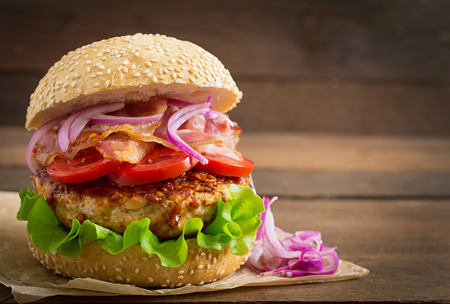 hamburguesa: Emparedado grande - hamburguesa hamburguesa con carne de res, cebolla roja, tomate y tocino frito