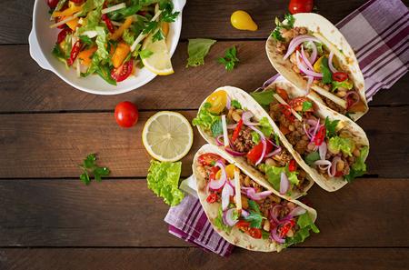 食べ物: 肉と豆のサルサのタコス。トップ ビュー