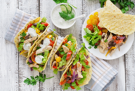 Mexican tacos with chicken, bell peppers, black beans and fresh vegetables. Top view