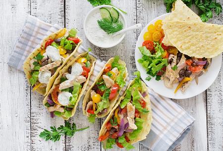 pollo: Tacos mexicanos con pollo, pimientos, frijoles negros y verduras frescas. Vista superior Foto de archivo