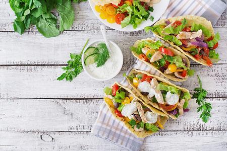 lechuga: Tacos mexicanos con pollo, pimientos, frijoles negros y verduras frescas y salsa t�rtara. Vista superior Foto de archivo