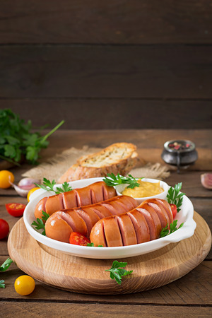 Sausages on the grill with vegetables on a platter 免版税图像