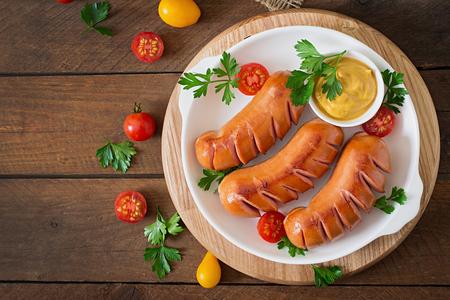embutidos: Salchichas en la parrilla con verduras en un plato. Vista superior