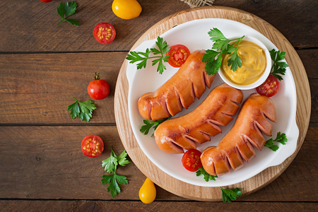 Sausages on the grill with vegetables on a platter. Top view